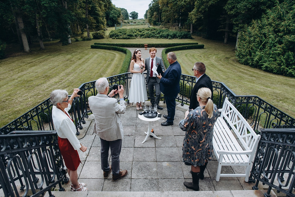 A group of people staying arounde newlyweds during their castle wedding in Denmark.