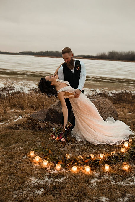 Newlyweds dancing in a romantic Nordic landscape lit with candles during their small intimate wedding abroad.