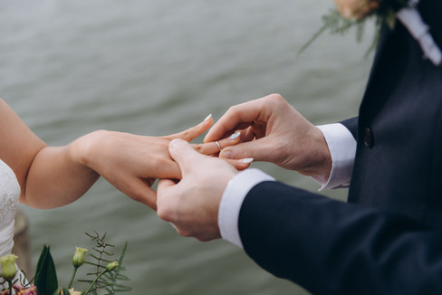 A couple exchanging vows and holding hands during their wedding abroad in Denmark.