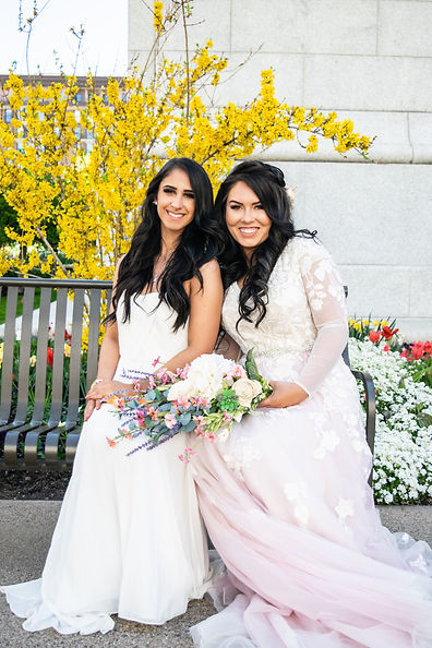 two-girls-in-a-wedding-dresses-sitting-close-to-each-other