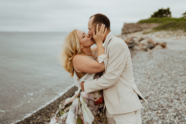 Husband and wife kissing passionately by the Baltic Sea while getting married in Denmark