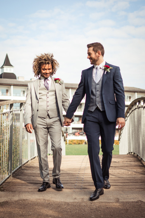 A gay couple walking across the bridge, holding hands while getting married in Denmark during their same-sex wedding adventure.