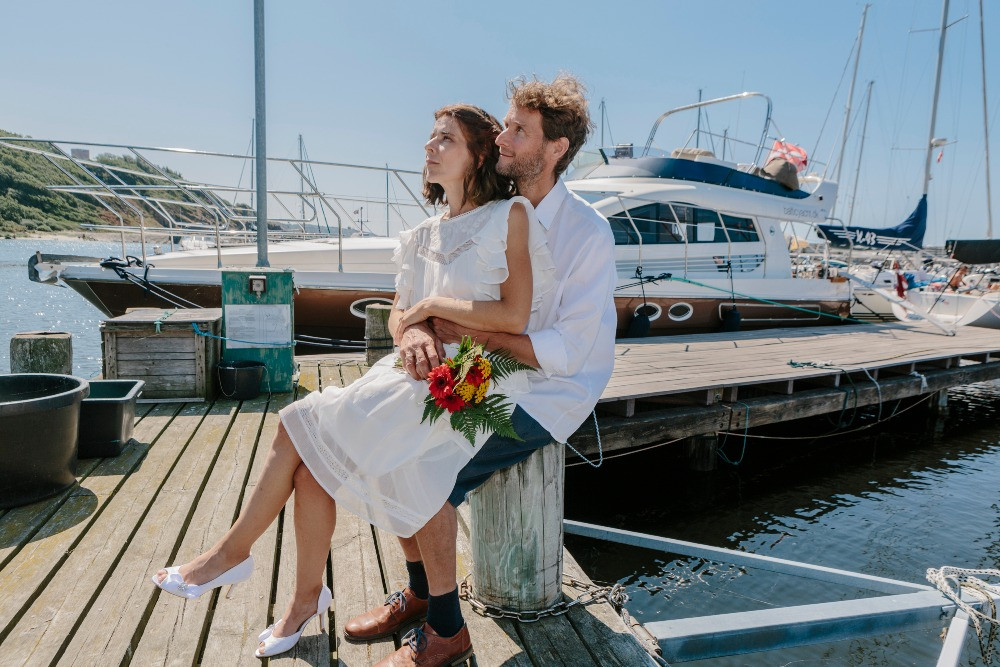 The bride sits on the groom's lap, during their adventure elopement on Bornholm.