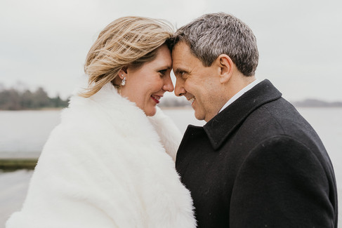 A close and intimate moment between a couple as they gaze deeply into each other's eyes and smile during their winter adventure wedding to Denmark.