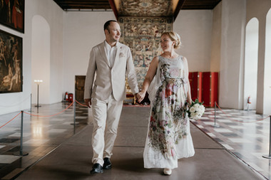 Husband and wife walking inside Hamlet's Elsinore Castle, one of the best places to elope and get married abroad in Denmark