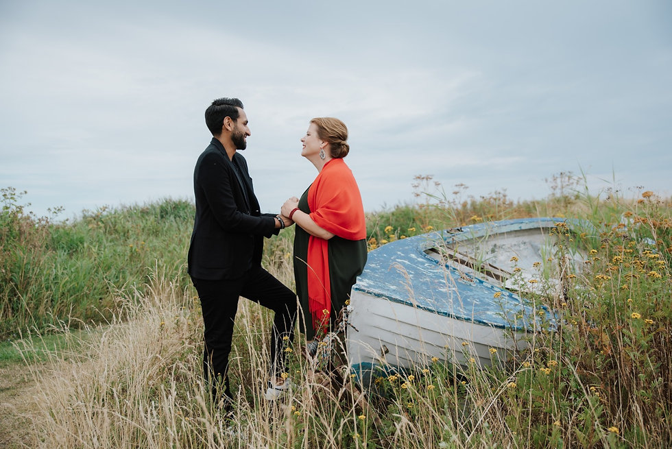 A couple holding hands in nature by a boat in the field as they smile and enjoy their vows renewal abroad in Denmark on Lolland Island.
