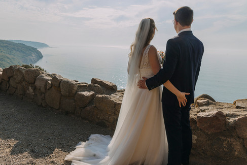 Newlyweds with arms around each other's waists as they look out at the Baltic Sea from the top of the Hammershus Ruins on Bornholm Island, a great marry abroad idea for couples that want an adventure elopement in Denmark.