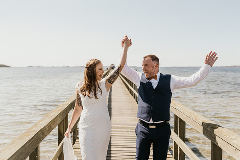Newlyweds lifting up their hands in joy during their beach wedding at the Hestehoved Jetty with our Denmark elopement packages