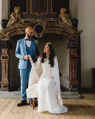 A groom and bride pose in  Hamlet's Elsinore Castle for their castle wedding portraits.