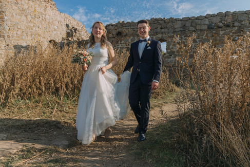 Newlyweds walking through the Hammershus Ruins and smiling as they get married in Denmark, one of the best places to elope in Europe.