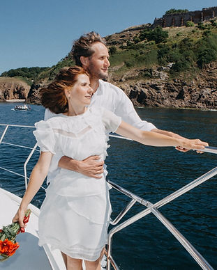 A couple on the yacht looking at the sea, performing their wedding package abroad for 2