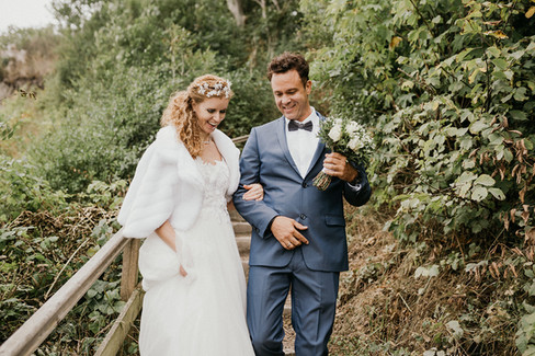 A bride and groom roaming the natural paths of Stevens Klint during their elopement in Denmark, a destination wedding location that you can book with one of our wedding packages abroad for two.