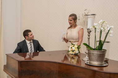 A groom playing the piano for his bride at the Bandholm Hotel in Denmark as they enjoy their wedding in Denmark