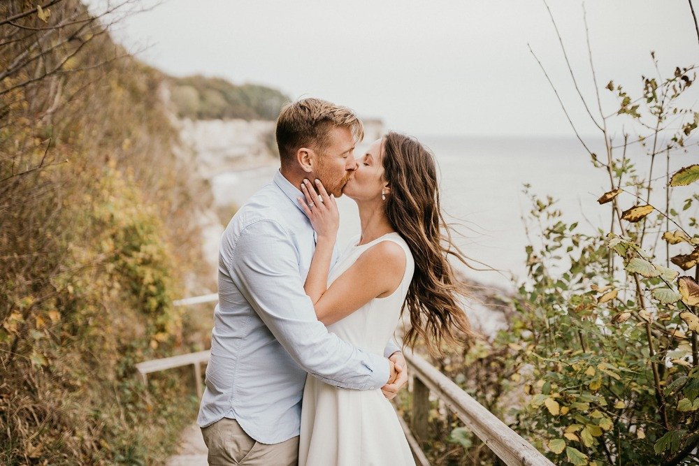 Canadian couple kissing in the front of cliffs since they getting married in Denmark