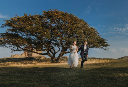 A couple running through the Hammershus Ruins on Bornholm Island during their Nordic wedding.