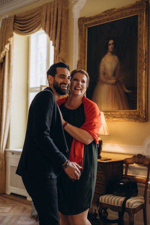 Man and wife laughing and leaning in towards each other, showing they had a great time during their vow renewal abroad in Denmark.