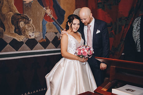 A groom embracing his bride while they are getting married in Copenhagen's City Hall.