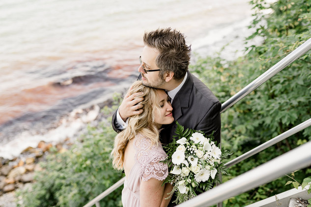 A groom hugging his wife by the Baltic Sea during their adventure wedding to Stevens Klint, their marry abroad idea.