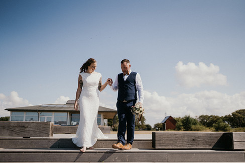 Husband and wife holding hands as they explore Lolland Island in Denmark during their elopement abroad.