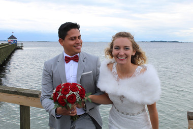 Newlyweds posing by the water and smiling during their beach wedding in Denmark as they enjoy getting married abroad.