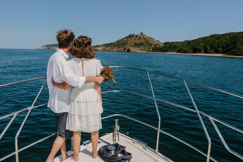 A couple looking into horisont from the yacht while they just had all inclusive elopement package at their Scandinavian wedding abroad.
