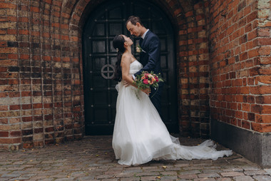 A portrait of husband and wife looking into each other's eyes and embracing during their small wedding abroad in Denmark on Lolland Island, one of the best places to elope abroad.