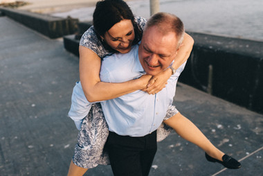 A husband giving a piggy back ride to his wife during their vow renewal abroad adventure in Lokken, Denmark, a lovely town also perfect for destination weddings.
