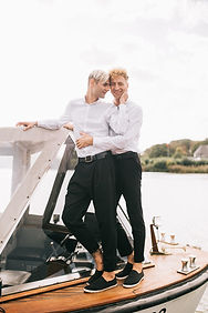 A gay couple looking at each other while they are on the boat after their gay destination wedding abroad
