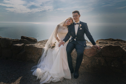 A bride leaning on her husband's shoulder as they sit on the edge of a stone wall at Hammershus Ruins overlooking the Baltic Sea during their adventure elopement in Bornholm Island in Denmark, a top wedding venue for intimate weddings abroad.