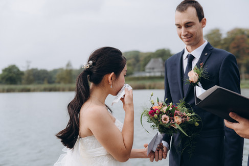 A bride laughing with her groom during their adventure wedding in Denmark by the Maribo Lake on Lolland Island.