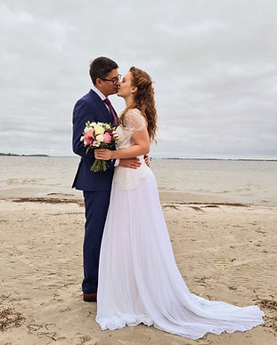 A couple kissing passionately on a quiet Nordic beach during their small wedding abroad.