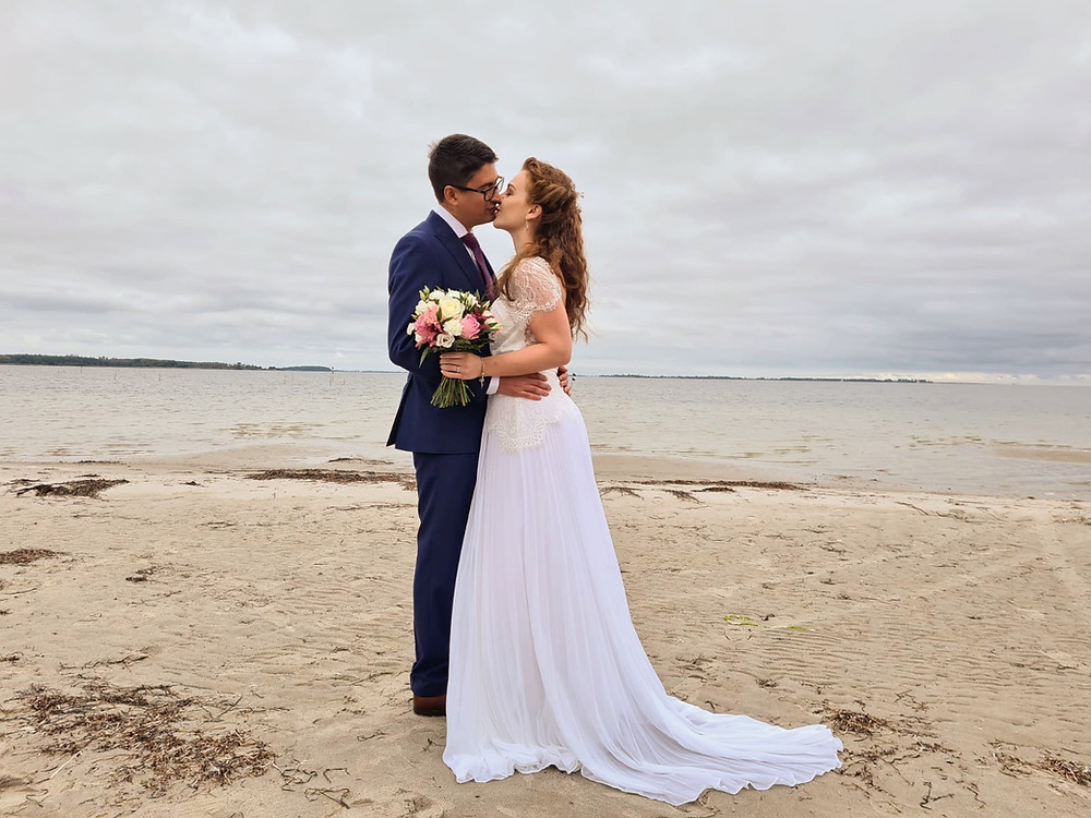 A groom kissing his bride at the Danish beach after they got married in Denmark in Maribo.