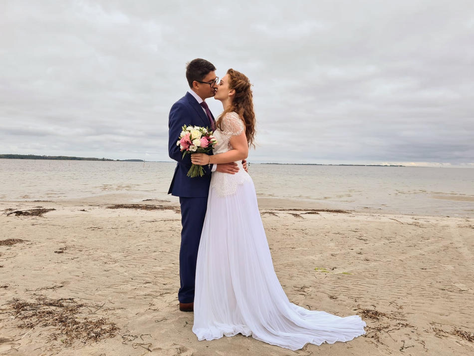 A couple kissing on the quiet Nordic beach during their marriage island adventure beach wedding abroad.