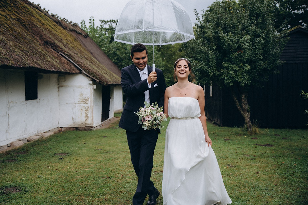 A groom holding an umbrella for his bride, getting married quickly,  during their elopement abroad.