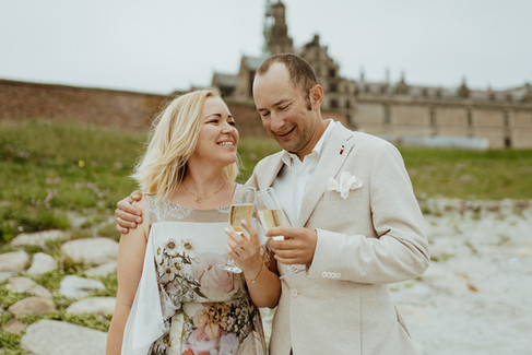 Husband and wife toasting as they renew vows abroad at Hamlet's Elsinore Castle in Denmark, one of the best places to elope for an intimate wedding abroad.