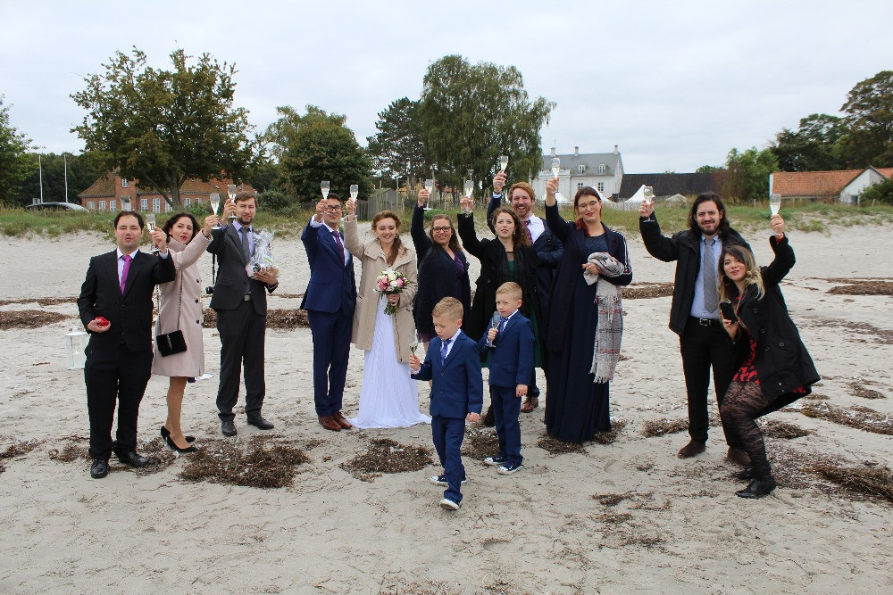 A group of wedding guests posing at the beach in Denmark