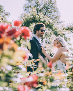 A couple being playful in a romantic rose garden as a part of their intimate Denmark wedding package abroad.