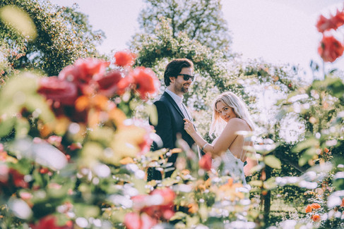 A bride playfully pulls at her husband's tuxedo during their adventure elopement to the rose gardens at the Lolland-Falster islands, one of the best places to elope for small weddings abroad.