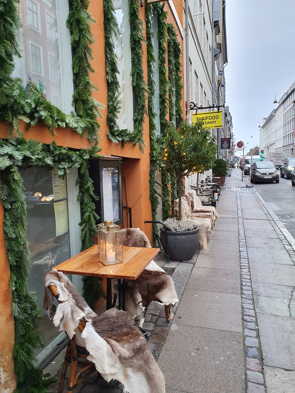 A street in Copenhagen with cafe tables and candels as a proof of the Danish hygge