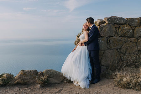 A groom embracing his bride at Bornholm Island's Hammershus Ruins during their all-inclusive destination wedding.