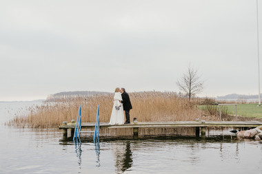 Newlyweds kissing by the pier at Lolland Island during their dream winter wedding in Denmark