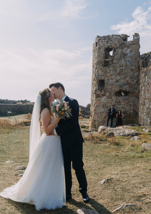 A couple kissing passionately at the Hammershus Ruins on the bridal island of Bornholm as they enjoy their intimate wedding abroad as a part of our wedding packages for two in Denmark.