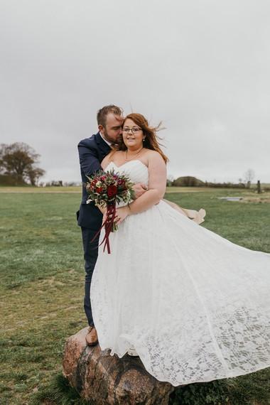 A groom hugging his bride from behind as they enjoy their Lolland Island wedding  in Denmark.