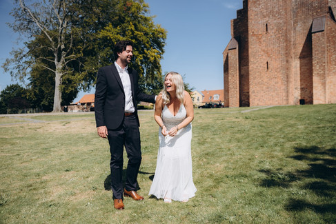 Newlyweds laughing by the Great Cathedral in Maribo as they explore the Lolland-Falster islands in Denmark during their adventure elopement.