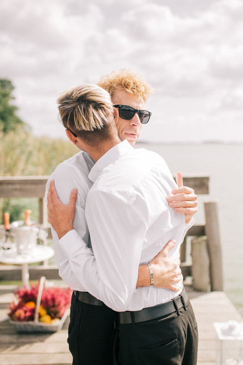 Two grooms hugging as they celebrate their same-sex wedding in Denmark, one of the best destinations for LGBT