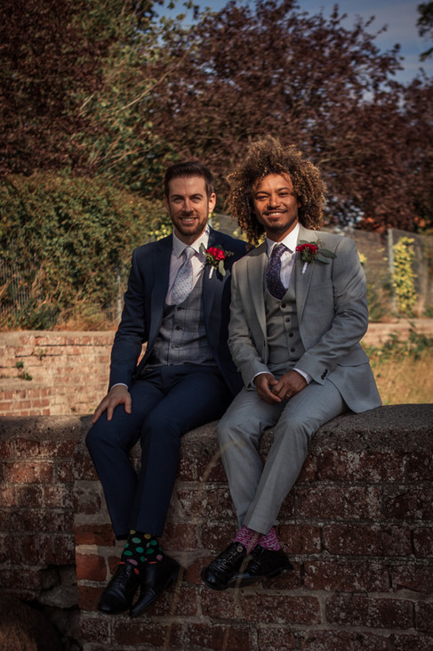 A couple sitting on a brick wall and smiling during their gay marriage in Denmark.