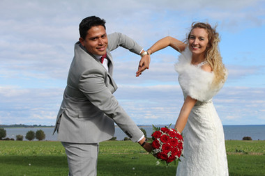 Newlyweds making a heart shape by joining hands during their adventure elopement to the twin islands of Lolland-Falster in Denmark