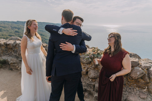 A celebration with the groom hugging his friends during their intimate wedding abroad at Bornholm Island, one of the best places to elope in Europe.