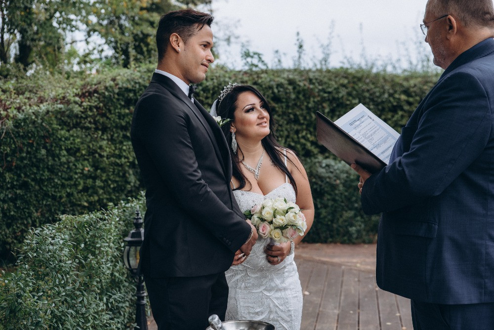 A couple listen to the wedding vows at their outdoor green wedding.