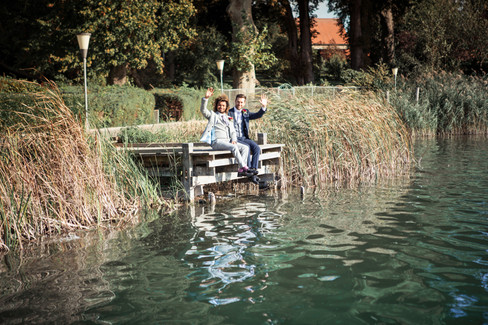 A gay couple waving at the camera while sitting by the lake in the heart of nature during their LGBT wedding adventure in Denmark.